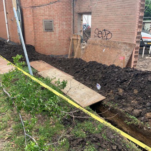 trench digging along commercial property for drainage project